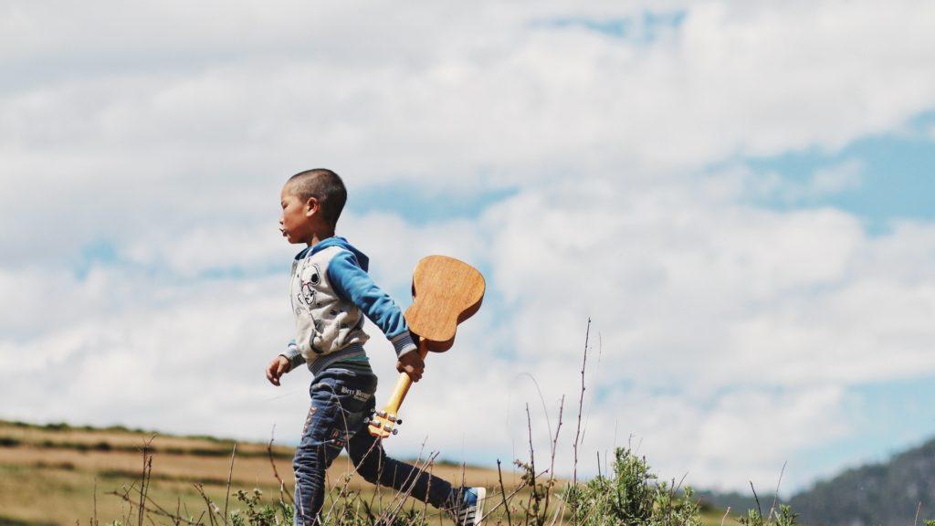 niño con ukelele aprende música